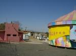 Otra vista de sanitarios y juegos y al fondo calle hacia El LLano