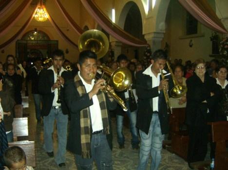 La banda de Ichán entra al templo en Ziquítaro, con la peregrinación de El Mirador, la víspera de la fiesta guadalupana